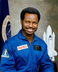 Posed photo of Ronald McNair in his NASA jumpsuit with an image of the space shuttle behind him.