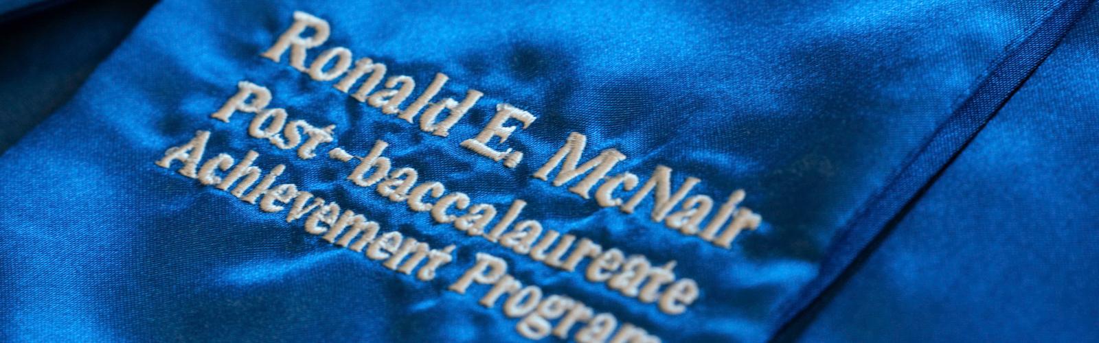 "A blue graduation stole with white lettering reading ""Ronald E. McNair Postbaccalaureate Achievement Program"""